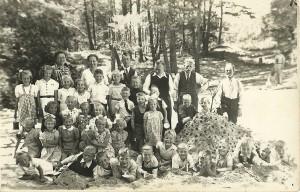 """Op de schoolreisfoto in de zandverstuiving van Appelscha liggen vooraan vanaf de vierde plek achtereenvolgens """"de makke schapen"""" Gerrit, Eddy, Anne en Jouke. Links achteraan staat juffrouw De Bildt, met rechts van haar achtereenvolgens juffrouw Reinbergen, Lammert Moll, meester Wapstra, Euwe Nijboer en Age Hoekstra. Drie leerkrachten en vier oudercommissieleden hielden met gemak de 34 kinderen van klas 1, 2 en 3 van de lagere school in Kortezwaag in toom."""