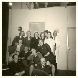 Op de foto rechts staan v.l.n.r. Hendrik (Bras) Veenstra, mevrouw Veenstra, Sietske van der Meulen de Jong, Sytske de Vries, Eddy van der Meulen, Geertje Stoelwinder, kapper Anne van der Muur (grimeur) en daarvoor Froukje Slof, Wiebe Lageveen, regisseur mevrouw Teyema en Annigje Dijkstra Kluitenberg. Vooraan zitten Jelle Stoelwinder en Tinus Dijkstra. Jelle verzorgde met een partner ook nog vaak de dansmuziek van het bal na.